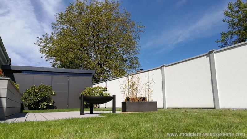 Modulare-Wandsysteme-neben-einem-Biohort-Gartenhaus-mit-Terrasse-und-Feuerschale-als-Fertigwand
